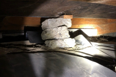 An improper and partially displaced support in a crawl space